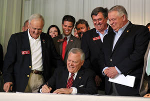 Photo - Surrounded by bill supporters, Georgia Gov. Nathan Deal signs House Bill 60 into law during a signing event Wednesday, April 23, 2013, in Ellijay, Ga. The bill makes several changes to the state's gun law. It allows those with a license to carry to bring a gun into a bar without restriction and into some government buildings that don't have certain security measures. It also allows religious leaders to decide whether it's OK for a person with a carry license to bring a gun into their place of worship. (AP Photo/Atlanta Journal-Constitution, Brant Sanderlin)  MARIETTA DAILY OUT; GWINNETT DAILY POST OUT; LOCAL TV OUT; WXIA-TV OUT; WGCL-TV OUT