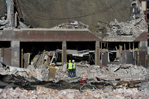 photo -   Inspectors stand in debris, Saturday, Nov. 24, 2012, at the site of a gas explosion that leveled a strip club in Springfield, Mass., on Friday evening. Investigators were trying to figure out what caused the blast where the multistory brick building housing Scores Gentleman's Club once stood. (AP Photo/Jessica Hill)
