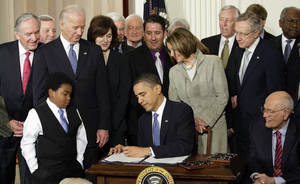 Photo - FILE - In this March 23, 2010 file photo, Marcelas Owens of Seattle, left, Rep. John Dingell, D-Mich., right, and others, look on as President Barack Obama signs the health care bill in the East Room of the White House in Washington. Medical claims costs _ the biggest driver of health insurance premiums _ will jump an average 32 percent for individual policies under President Barack Obama's overhaul, according to a study by the nation's leading group of financial risk analysts. Recently released to its members, the report from the Society of Actuaries could turn into a big headache for the Obama administration at a time when many parts of the country remain skeptical about the Affordable Care Act.  (AP Photo/J. Scott Applewhite, File)