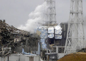 "Photo -   FILE - In this March 15, 2011 file photo released by Tokyo Electric Power Co., smoke rises from the badly damaged Unit 3 reactor, left, next to the Unit 4 reactor covered by an outer wall at the Fukushima Dai-ichi nuclear complex in Okuma, northeastern Japan. The emergency command center at Japan's stricken nuclear plant shook violently when hydrogen exploded at Unit 3 and the plant chief reacted by shouting, ""This is serious, this is serious,"" reveal videos of the crisis as it happened last year. (AP Photo/Tokyo Electric Power Co., File)"