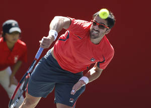 Photo -   Janko Tipsarevic of Serbia serves to Marco Chiudinelli of Switzerland during their second round match of the Japan Open tennis championships in Tokyo Thursday, Oct. 4, 2012. Tipsarevic won the match, 6-4, 6-2. (AP Photo/Shuji Kajiyama)