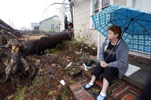 Photo - Hellen Chmiel, 57, sits in front of the remains of her home in Hattiesburg, Miss., Monday, Feb. 11, 2013, following a Sunday afternoon tornado that caused much damage throughout the South Mississippi college town. Chmiel, who was out of her house when the tornado struck, said the large pine tree in the front yard completely destroyed her bedroom. (AP Photo/Rogelio V. Solis)