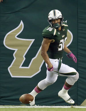 Photo - South Florida defensive back Nate Godwin (36) celebrates after returning a blocked field goal 75-yards for a touchdown during the first quarter of an NCAA college football game against Cincinnati on Saturday, Oct. 5, 2013, in Tampa, Fla. (AP Photo/Chris O'Meara)