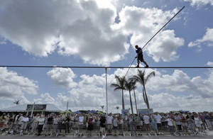 Photo - A large crowd watches as high wire performer Nik Wallenda walks across a wire as he practices Tuesday, June 18, 2013 in Sarasota, Fla.  Wallenda, a seventh generation high-wire walker, will attempt to walk across the Grand Canyon on Sunday, June 23, 2013.  (AP Photo/Chris O'Meara)