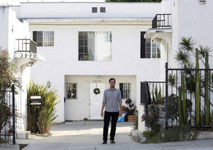 Photo - In this Thursday, March, 27, 2014 photo, Marc Caswell, who recently moved from San Francisco to Los Angeles, poses for a photo in front of his newly rented apartment in the Los Feliz district of Los Angeles. Rising rents in San Francisco compelled Marc Caswell to move to Los Angeles in September. (AP Photo/Damian Dovarganes)