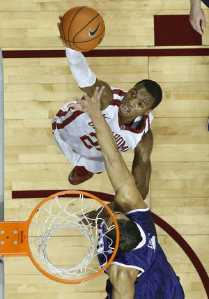 Photo - Oklahoma guard Buddy Hield (24) shoots in front of TCU forward Amric Fields during the first half of an NCAA college basketball game in Norman, Okla., Wednesday, Jan. 22, 2014. (AP Photo/Sue Ogrocki)