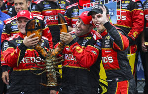 Photo - Brad Keselowski, right, gestures while celebrating with members of his team, holding a lobster, in Victory Lane after winning the NASCAR Sprint Cup series auto race at New Hampshire Motor Speedway on Sunday, July 13, 2014, in Loudon, N.H. (AP Photo/Cheryl Senter)