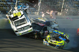 Photo - Parker Kligerman (30) gets airborne as he is involved in a crash with Ryan Truex (83), Paul Menard (27), and Dave Blaney (77) during practice for Sunday's NASCAR Daytona 500 Sprint Cup Series auto race at Daytona International Speedway, Wednesday, Feb. 19, 2014. (AP Photo/News-Journal, Nigel Cook)