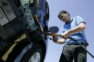 Photo - Garvin Cui fuels up his natural gas vehicle at a Clean Energy station in San Francisco.  AP Photo