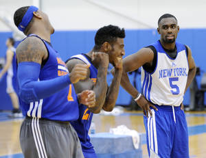 Photo - New York Knicks' Tim Hardaway, Jr. (5) looks on as Iman Shumpert and Carmelo Anthony, left, react to their shooting drill at the teams NBA basketball training camp Tuesday, Oct. 1, 2013, in Greenburgh, N.Y. (AP Photo/Bill Kostroun)