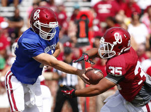 Photo - Oklahoma quarterback Justice Hansen (4) hands off a pass to running back Leo Luna (35) during the second half of the annual Oklahoma Spring Football game in Norman, Okla. on Saturday, April 12, 2014. (AP Photo/Alonzo Adams)