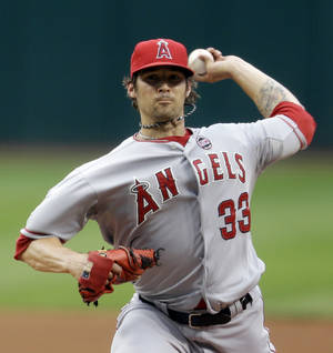 Photo - Los Angeles Angels starting pitcher C.J. Wilson delivers in the first inning of a baseball game against the Cleveland Indians, Saturday, Aug. 10, 2013, in Cleveland. (AP Photo/Tony Dejak)