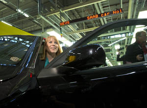 Photo - Swedish Minister of Trade, Annie Loof, looks out from the first production Nevs (National Electric Vehicle Sweden) Saab 9-3 Aero at the Trollhattan factory in Sweden, Monday, Dec. 2, 2013. NEVS bought the remains of Swedish car maker SAAB and is focusing on electric vehicles. However the first car to leave the factory after it was restarted is a gasoline fueled 220 horsepower 2.0-liter turbo. (AP Photo/TT, Bjorn Larsson Rosvall)    SWEDEN OUT