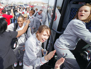 Photo - OU players (from left) Amanda Thompson, Carlee Roethlisberger and Whitney Hand board the bus as the Sooners leave the Lloyd Noble Center on Thursday. Over 100 fans cheered the team on their way to San Antonio, Texas, for the Final Four.  Photo by Steve Sisney, The Oklahoman