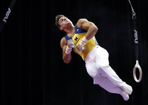 Photo - Sam Mikulak dismounts from the rings during the U.S. men's national gymnastics championships in Hartford, Conn., Friday, Aug. 16, 2013. (AP Photo/Elise Amendola)
