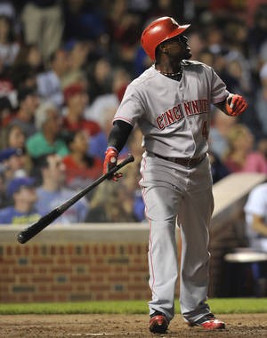 Photo - Cincinnati Reds' Brandon Phillips watches his two-run home run against the Chicago Cubs during the seventh inning of a baseball game, Monday, Aug. 12, 2013, in Chicago. (AP Photo/Jim Prisching)