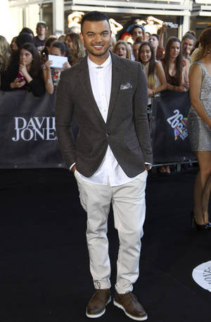 Photo - Guy Sebastian smiles at photographers upon arrival for the Australian music industry Aria Awards in Sydney, Thursday, Nov. 29, 2012. (AP Photo/Rick Rycroft)