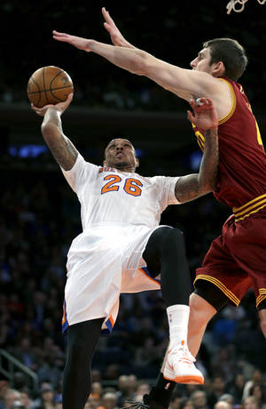 Photo - New York Knicks' Shannon Brown, left, puts up a shot while Cleveland Cavaliers' Tyler Zeller defends during the first half of an NBA basketball game at Madison Square Garden, Sunday, March 23, 2014, in New York. (AP Photo/Seth Wenig)