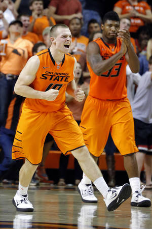 Photo - Oklahoma State's Phil Forte (10) and Marcus Smart (33) celebrate during the men's college basketball game between Oklahoma State and UC Davis at  Gallagher-Iba Arena in Stillwater, Okla., Friday, Nov. 9, 2012. Photo by Sarah Phipps, The Oklahoman