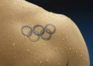 Photo -   In this Thursday, July 26, 2012 photo, water droplets fall across a tattoo of the Olympic rings on the shoulder of diver Illya Kvasha of Ukraine, during a diving practice session at the Aquatics Center at the Olympic Park ahead of the 2012 Summer Olympics, in London. (AP Photo/Matt Slocum)