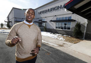 Photo - The Rev. MIchael Metcalf stands in front of the new LifeChurch.tv Moore, where he serves as campus pastor. <strong>STEVE SISNEY - THE OKLAHOMAN</strong>