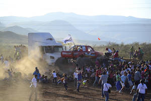 Photo - People run as an out of control monster truck plows through a crowd of spectators at a Mexican air show in the city of Chihuahua, Mexico, Saturday Oct. 5, 2013. According to authorities, at least 8 people were killed and 80 were injured. (AP Photo/El Diario de Chihuahua)