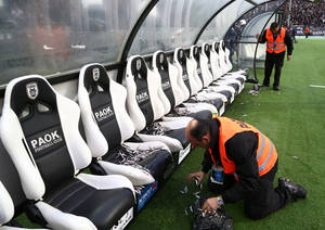 Photo - In this photo taken Wednesday, April 16, 2014 an employee of PAOK cleans Olympiakos' bench from fish before a semi-final of the Greek Cup in the northern port city of Thessaloniki. Police in Thessaloniki have arrested a PAOK fan accused of dumping a crate of fish on the visiting Olympiakos bench, in a jibe that delayed a tense Greek cup semi-final for more than an hour. Another six PAOK supporters were arrested during clashes with police before and after Thursday's match, which PAOK won 1-0 to advance on aggregate. The game was repeatedly halted by on-turf brawls, resulting in three red cards, while PAOK fans in the stands lit thousands of flares, and several were thrown on the pitch. (AP Photo/InTime Sports, Yorgos Matthaios)  GREECE OUT