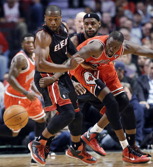 Photo - Miami Heat guard Dwyane Wade, left, forward LeBron James, center, and Chicago Bulls forward Luol Deng watch a loose ball during the first half of an NBA basketball game in Chicago on Wednesday, March 27, 2013. (AP Photo/Nam Y. Huh)