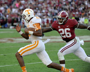 Photo - In this photo taken  Oct. 26, 2013, Tennessee quarterback Josh Dobbs is pursued by Alabama defensive back Landon Collins during a NCAA football game in Tuscaloosa, Ala. (AP Photo/Michael Patrick, Knoxville News Sentinel)