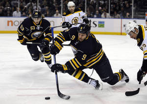 photo - Buffalo Sabres' center Steve Ott (9) dives to pass the puck on a face-off against Boston Bruins center Chris Kelly (23) as Sabres Tyler Ennis (63) and Bruins' Patrice Bergeron (37) look on during the first period of an NHL hockey game in Buffalo, N.Y., Friday, Feb. 15, 2013. (AP Photo/Gary Wiepert)