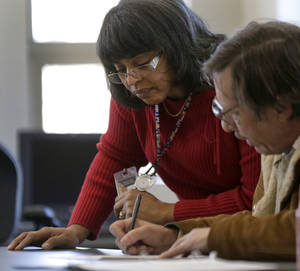 Photo - Caseworker Cheryl Boone helps a client with paperwork during a therapy session at the Johnson County Mental Health Center Wednesday, Jan. 23, 2013, in Shawnee, Kan. Lawmakers across the nation are rethinking cuts in mental health care spending in the wake of recent shootings. (AP Photo/Charlie Riedel)