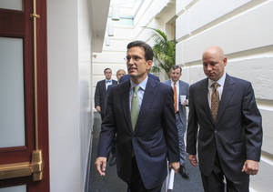 Photo - In this Sept. 10, 2013, photo, House Majority Leader Eric Cantor, R-Va., walks to a Republican strategy session at the Capitol, in Washington. A revolt by tea party conservatives forced House GOP leaders on Wednesday, Sept. 11, to delay a vote on a temporary spending bill required to prevent a government shutdown next month. The plan by top Republicans like Cantor is designed to keep government agencies running through Dec. 15. Cantor's office announced the delay. (AP Photo/J. Scott Applewhite)