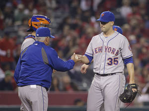 Photo - New York Mets starting pitcher Dillon Gee, right, hands the ball to manager Terry Collins as he is relieved during the sixth inning of a baseball game against the Los Angeles Angels on Friday, April 11, 2014, in Anaheim, Calif. (AP Photo/Jae C. Hong)