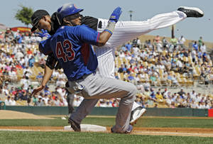 Photo - Chicago Cubs' Emilio Bonifacio (43) collides with Chicago White Sox second baseman Marcus Semien covering first on a bunt in the first inning of a spring exhibition baseball game Friday, March 21, 2014, in Glendale, Ariz. (AP Photo/Mark Duncan)