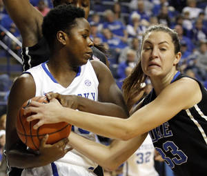 Photo - Kentucky's Samarie Walker, left, is tied up by Duke's Haley Peters during the first half of an NCAA college basketball game, Sunday, Dec. 22, 2013, in Lexington, Ky. Kentucky won 93-80. (AP Photo/James Crisp)