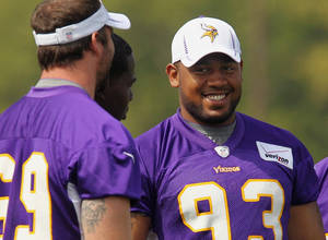 Photo - Vikings defensive tackle Kevin Williams, right, shares a laugh with teammate Jared Allen during camp. AP photo