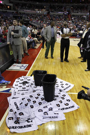 Photo - Towels and trash cans are used to catch water dripping from the ceiling in the first half of an NBA basketball game between the Houston Rockets and the Washington Wizards, Saturday, Jan. 11, 2014, in Washington. (AP Photo/Alex Brandon)