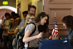 Photo -   College student Cortney Ratashak, 18, of Littleton, Colo., talks over paperwork with an electoral official before voting in the general election, at a polling station serving the local student population on the campus of the University of Colorado, in Boulder, Colo., Tuesday, Nov. 6, 2012. After a grinding presidential campaign, Americans are heading into polling places across the country.(AP Photo/Brennan Linsley)