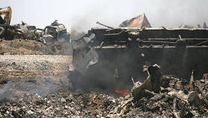 Photo -   Train wreckage still smolders on Monday, June 25, 2012, near Goodwell, Okla. Two Union Pacific trains collided on Sunday, June 24, 2012, killing two crew members and a conductor. (AP Photo/The Guymon Daily Herald, Shawn Yorks)