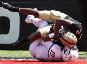 Photo - Purdue cornerback Frankie Williams (24) intercepts a pass  in the end zone intended for Cincinnati receiver Shaq Washington (19) during the second half of an NCAA college football game, Saturday, Aug. 31, 2013, in Cincinnati. Cincinnati won 42-7. (AP Photo/Al Behrman)