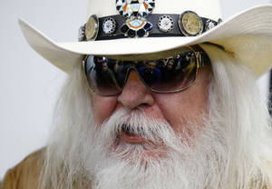photo - Reporters are reflected in the sunglasses of Leon Russell as he answers a question at a news conference in Tulsa, Okla., Tuesday, Jan. 29, 2013. The Oklahoma Historical Society has acquired a large collection of works by the legendary musician and native Oklahoman that are intended for display in a planned pop culture museum in Tulsa. (AP Photo/Sue Ogrocki)