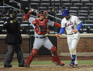 Photo - Washington Nationals catcher Jose Lobaton, center, throws the ball back to the mound after New York Mets' David Wright (5) struck out in the ninth inning of a baseball game at Citi Field on Wednesday, April 2, 2014, in New York. The Nationals won 5-1. (AP Photo/Kathy Kmonicek)