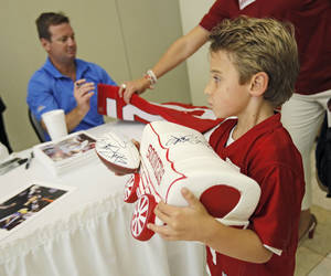 Photo - Trey Dallas, 6, of Edmond, walks away after getting an autograph from OU football coach Bob Stoops during the Sooner Caravan stop at the National Cowboy & Western Heritage Museum on Thursday. (Photo by Bryan Terry, The Oklahoman)