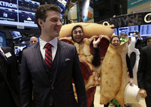 Photo - GrubHub Inc. CEO Matthew Maloney, trailed by costume characters, walks the New York Stock Exchange trading floor before his company's IPO begins trading, Friday, April 4, 2014. Investors sent shares of the online food ordering service up 51 percent to $39.20 in early trading in its stock market debut Friday. (AP Photo/Richard Drew)