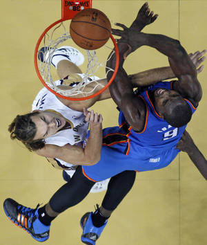 Photo - Oklahoma City Thunder power forward Serge Ibaka (9) goes to the basket against New Orleans Pelicans power forward Lou Amundson in the second half of an NBA basketball game in New Orleans, Friday, Dec. 6, 2013.  The Thunder won 109-95. (AP Photo/Gerald Herbert)