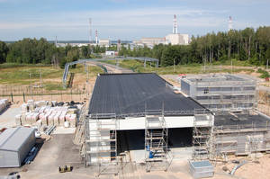 Photo -   This July 2012 photo shows the gatehouse of the partially-completed nuclear storage facility in Ignalina, Lithuania. Three years after the nuclear plant was shut down due to safety concerns, there is still nuclear fuel inside one of the two reactors. The temporary storage facilities for spent fuel and radioactive waste are four years behind schedule. The problems have prompted threats from the European Union to sever funding and raising concerns that the facility will be around for years, possibly decades, longer than planned. The giant ventilation stacks in the background are part of the nuclear power plant. (AP Photo/Gary Peach)