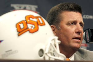 Photo - Oklahoma State University football coach Mike Gundy addresses the media at the beginning of the Big 12 Conference Football Media Days Monday, July 22, 2013 in Dallas.  (AP Photo/Tim Sharp) ORG XMIT: TXTS105