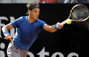 Photo - Spain's Rafael Nadal returns the ball to Russia's Mikhail Youzhny during their match at the Italian Open tennis tournament, in Rome, Thursday, May 15, 2012. (AP Photo/Andrew Medichini)