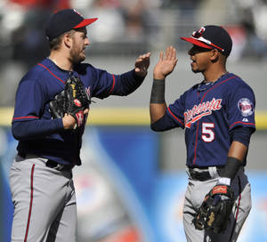 Photo - Minnesota Twins closing pitcher Glen Perkins left, celebrates with teammate Eduardo Escobar (5) after defeating the Chicago White Sox 5-3 in a baseball game in Chicago, April 21, 2013. (AP Photo/Paul Beaty)
