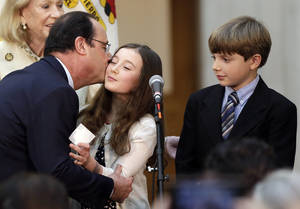 Photo - French president Francois Hollande, left, kisses a girl on the stage during a visit to city hall on Wednesday, Feb. 12, 2014, in San Francisco. Hollande is visiting San Francisco to meet politicians, lunch with Silicon Valley tech executives and inaugurate a new U.S.-French Tech Hub. (AP Photo/Marcio Jose Sanchez)